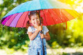 Happy child girl laughs and plays under summer rain with an umbrella. Royalty Free Stock Photo