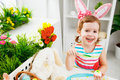 Happy child girl paints eggs for Easter