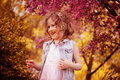 Happy child girl in pink dress playing outdoor in spring garden near blooming crabapple tree Royalty Free Stock Photo