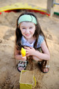 Happy child girl is playing in a sandbox Stock Photography
