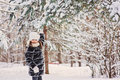 Happy child girl plays with snow on pine tree in winter forest faux fur coat Royalty Free Stock Photography