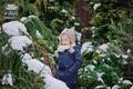 Happy child girl plays in winter snowy garden