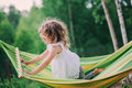 Happy child girl relaxing in hammock on summer camp in forest. Outdoor seasonal activities Royalty Free Stock Photo