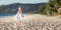 Happy child girl running on beach by sea in summer Royalty Free Stock Photo