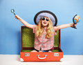 Happy child girl is sitting in pink suitcase holding a globe and magnifying glass. Travel and adventure concept