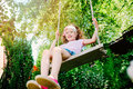 Happy child girl on swing, activities on summer vacation Royalty Free Stock Photo