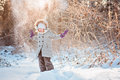 Happy child girl throwing snow in winter sunny forest cute on the walk Stock Image