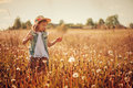 Happy child girl walking on summer meadow with dangelions. Rural country style scene, outdoor activities. Royalty Free Stock Photo