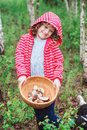 Happy child girl with wild edible wild mushrooms on wooden plate Royalty Free Stock Photo