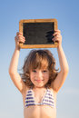 Happy child holding blank blackboard against blue sky background summer vacations concept Royalty Free Stock Photo