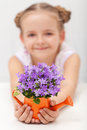 Happy child holding fresh spring flowers small watering can Royalty Free Stock Image