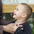 Happy child holding parent hand toddler of his and smiling up to him Royalty Free Stock Image