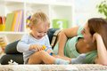Happy child holds animal toy playing with mom in Royalty Free Stock Photo