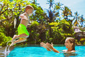 Happy child jump to mother hands in swimming pool
