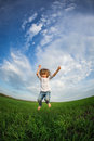 Happy child jumping in green field against blue sky summer vacation concept Royalty Free Stock Photos