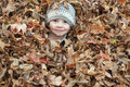 Happy child in the leaves little boy buried a pile of with just his face sticking out he is smiling and and wearing a crocheted Stock Image