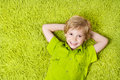 Happy child lying on the green carpet background Royalty Free Stock Photo