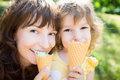Happy child and mother eating ice cream outdoors in summer park Royalty Free Stock Image