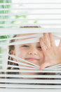 Happy child peeking through blinds window Stock Photo
