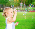 Happy child playing outdoors having fun in the park cute blond baby girl with soap bubbles on the yard joyful little kid enjoying Royalty Free Stock Image