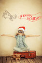 Happy child playing with toy airplane in santa claus hat at home retro toned Stock Photo