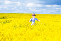 Happy child running in a field of yellow flowers laughing Royalty Free Stock Images