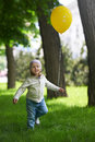 Happy child running with a yellow balloon Royalty Free Stock Photo