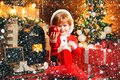 Photo : Happy child in santa clothes with ornament ball. Winter delivery service for kids. Having some Xmas fun. Christmas  scene