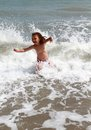 Happy child at sea with waves having fun Royalty Free Stock Image