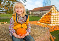 Happy child sitting on haystack with pumpkin portrait of Royalty Free Stock Image