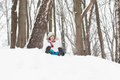 Happy child sledging from a snowy hill little Royalty Free Stock Images