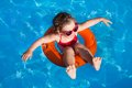 Happy child swimming funny little girl swims in a pool in an orange life preserver Stock Photo