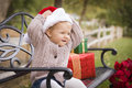 Happy child wearing santa hat sitting with christmas gifts outside young toddler on bench Royalty Free Stock Photos