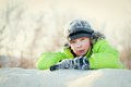 Happy child in winterwear smiling while playing in snowdrift teen outside Stock Image