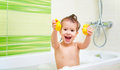 Happy child with yellow duck toys bathes in  bath with foam and Royalty Free Stock Photo