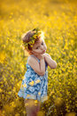 Happy childhood baby girl in wreath in field Stock Photo