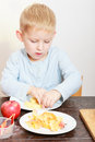 Happy childhood boy child kid eating peeled apple fruit at home preschooler or making batter for drop scones Royalty Free Stock Photo