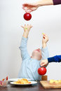 Happy childhood. Boy child kid reaching for apple fruit. At home. Stock Images