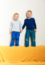 Happy childhood full length blond boys children on top of sofa smiling kids brothers playing at home Royalty Free Stock Images