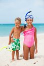 Happy children on beach two with colorful face masks and snorkels sea in background Stock Photos