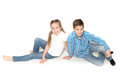 Happy children boy and girl sit lie on the floor and smiling studio photo on white background Royalty Free Stock Images