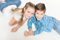 Happy children boy and girl sit lie on the floor and smiling studio photo on white background Stock Images