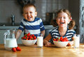 Happy children brother and sister eating strawberries with milk Royalty Free Stock Photo