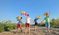 Happy children with colorful balloons in a field Stock Photography