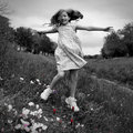 Jumping girl is having fun in a field with poppies