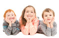 Happy children with head in hands three laying on floor resting on on white Royalty Free Stock Image