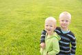 Happy children outdoor joyful beautiful two little caucasian blond boys brothers over green grass having fun sunny summer day copy Stock Image