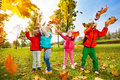 Happy children playing with flying leaves in park Royalty Free Stock Photo