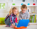Happy children playing with laptop at home