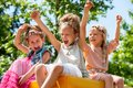 Happy children raising hands and shouting young girls together in park Royalty Free Stock Photography